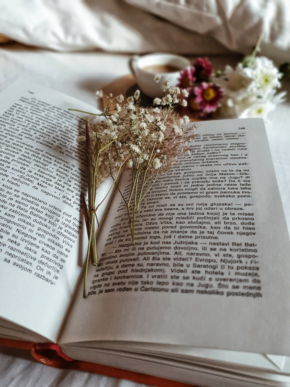 dried plants in opened book on cozy bed